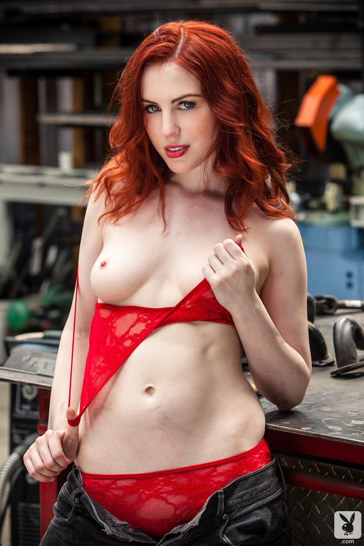 Horny redhead model strips in a big car garage